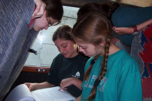 photo of 15-year-old me reading aloud to friends on a bus